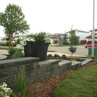 Garden pictures of the landscape design for a pie shaped lot including retaining walls and flower garden ideas.